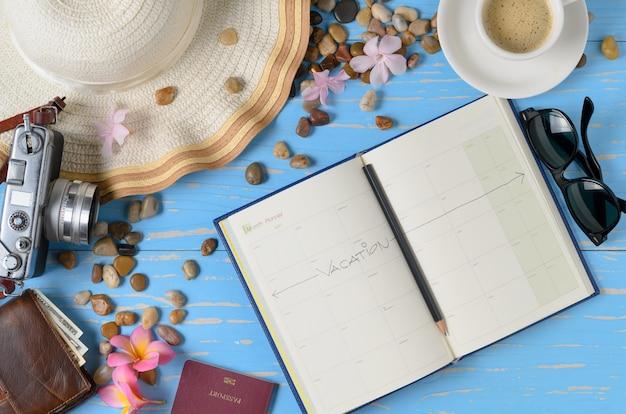 Plan para viajar en el libro de calendario con accesorios para viajar