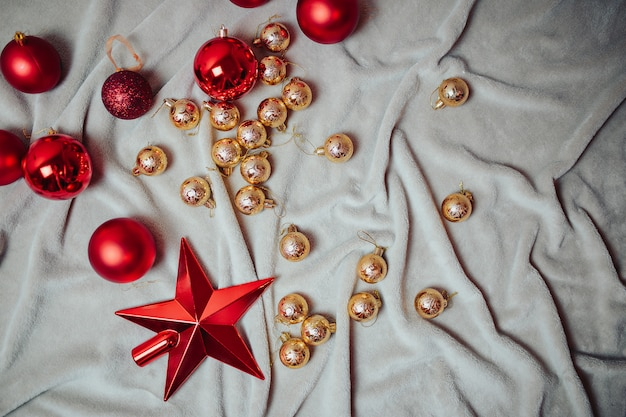 Plana con bolas rojas de navidad, bolas de navidad doradas y bastones de caramelo de navidad en la tela escocesa.