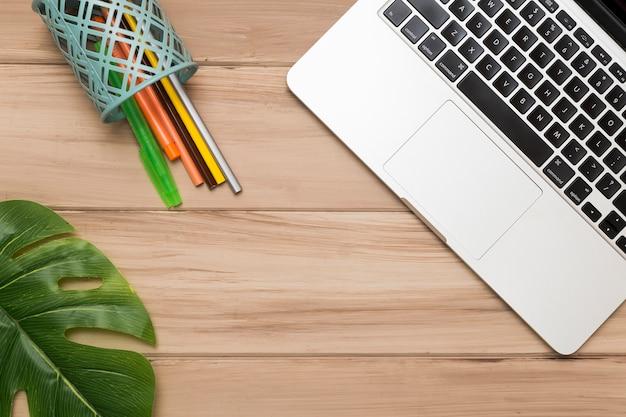 Plana creativa de escritorio de madera con laptop y bolígrafos de colores.