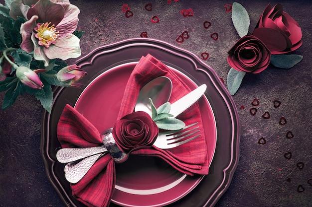 Plana con platos de color burdeos y vajilla decorada con rosas y anémonas, configuración de cena de navidad o san valentín