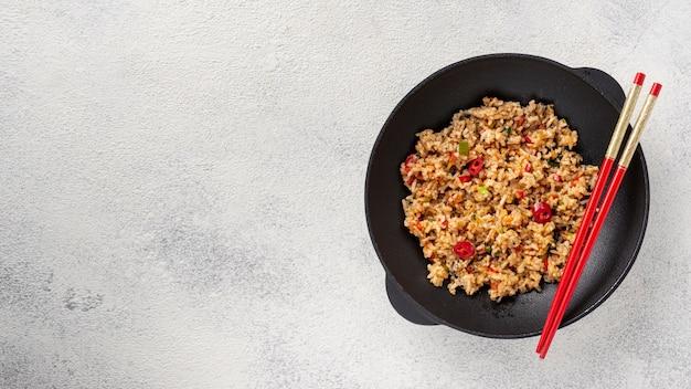 Plana pone arroz y verduras en un plato con palillos con espacio de copia