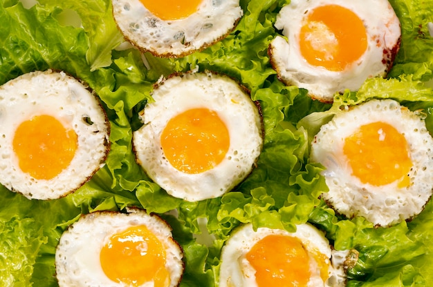 Plana pone huevos fritos con arreglo de ensalada verde