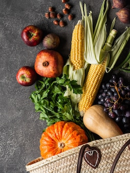 Plana pone verduras y frutas de temporada sobre fondo gris