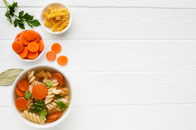 Plana pone zanahorias de brócoli y fusilli en un tazón con espacio de copia