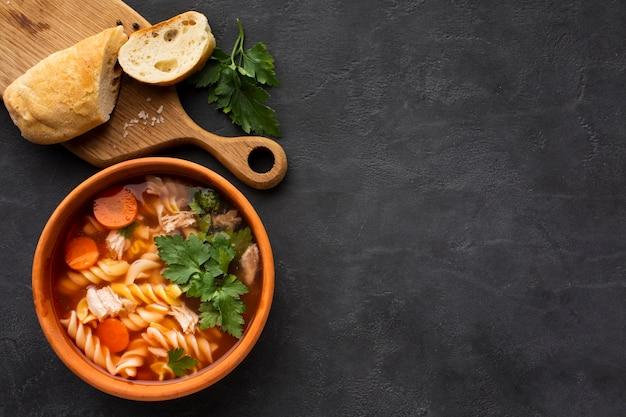 Plana pone zanahorias de brócoli y fusilli en un tazón con pan en la tabla de cortar con espacio de copia