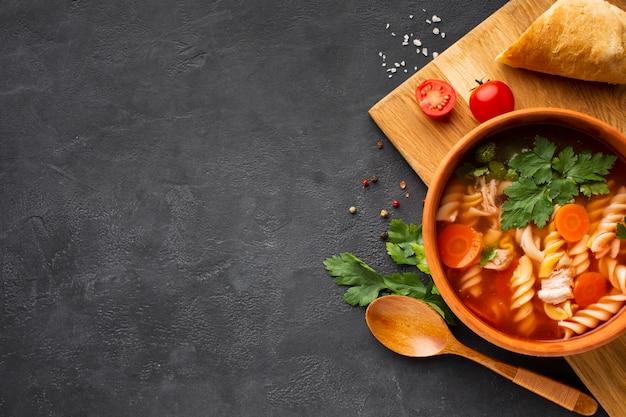 Plana poner zanahorias de brócoli y sopa fusilli en un tazón con pan de tomate y cuchara de madera con espacio de copia