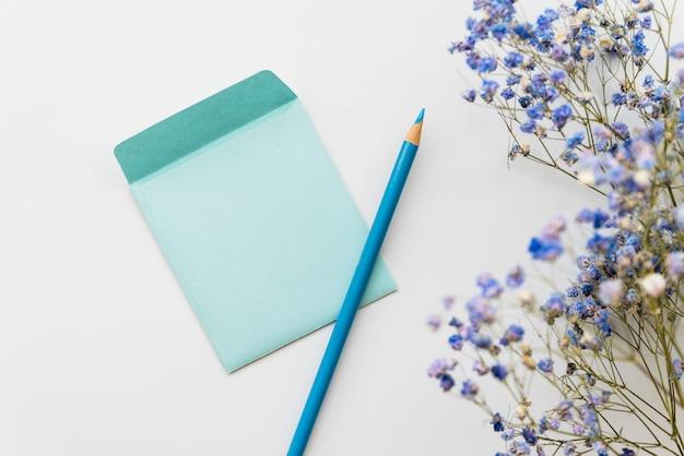 Plana puesta con flores y sobre con lápiz.