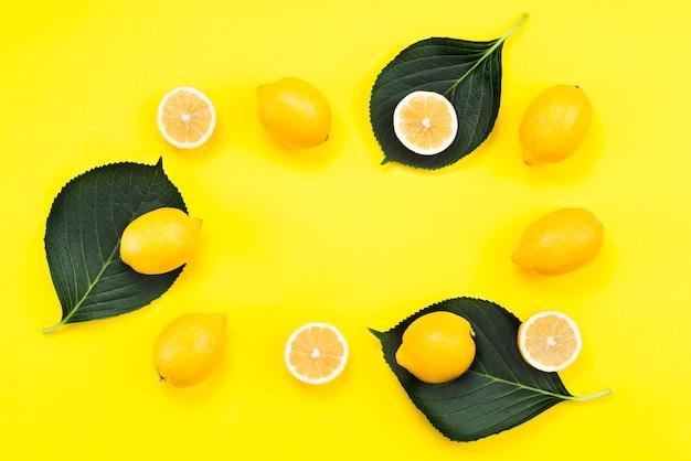 Plana puesta de limones maduros con hojas.