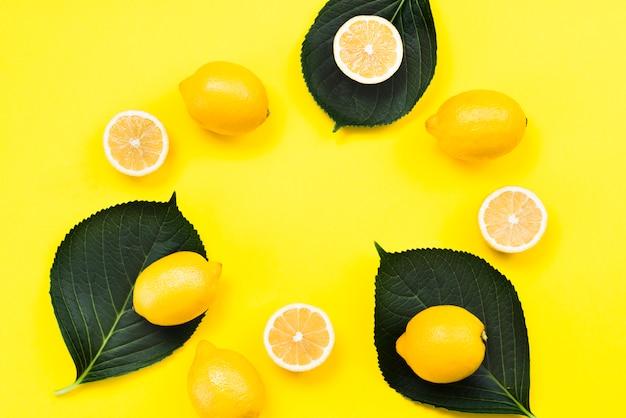 Plana puesta de limones tropicales sobre hojas.