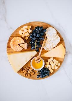 Plana con varios tipos de queso, uvas, nueces, miel y galleta en tabla de madera sobre mármol