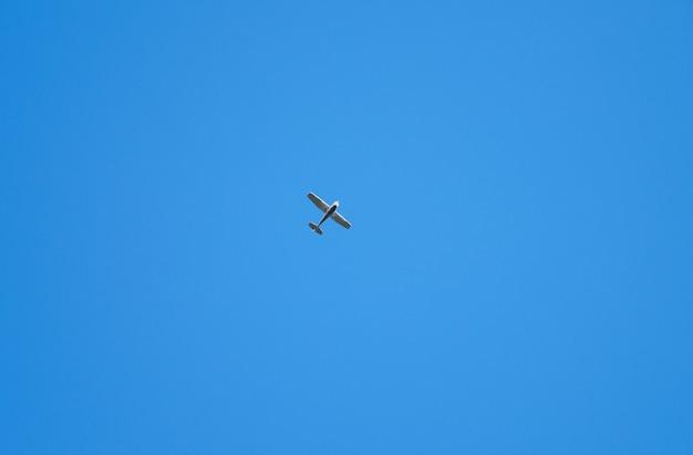 Planeador retro viejo solo alto contra el cielo azul. avión vuela en cielo despejado. aviación de aviones.