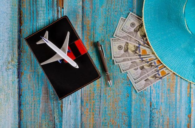 Planeamiento de viaje avión, lápiz, gorro azul y cuaderno de notas con preparación de espacio en blanco para viajar