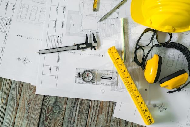 Planes de construcción con casco y herramientas de dibujo en planos.