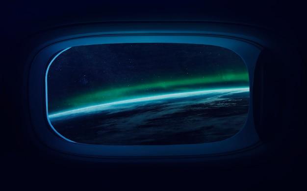 Planeta tierra en ojo de buey de ventana de nave espacial
