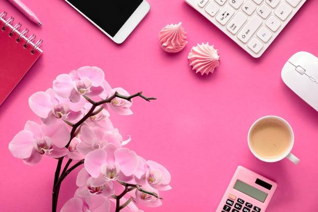 Planificación de la celebración: tarjetas de teléfono móvil, teclado, café e invitaciones con orquídeas en papel rosa