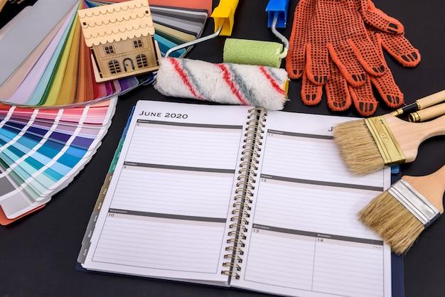Planificación de remodelación con diario y herramientas de pintura en la mesa.