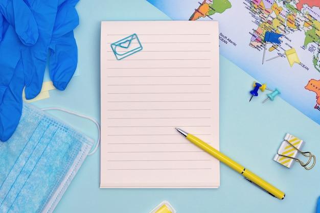 Planificación segura de viaje. máscara médica, guantes, artículos estacionarios y mapa sobre fondo azul con espacio de copia.
