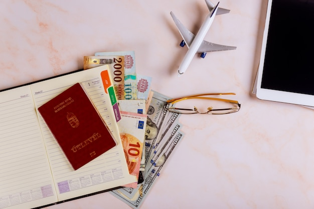 Planificación de un viaje, reserva de viajes, reserva de vuelos en la tableta táctil del dispositivo con pasaportes húngaros y billetes en dólares,