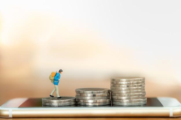 Planificación de viajes, concepto de dinero y tecnología. ciérrese para arriba de la figura miniatura del viajero con la mochila que camina en la pila superior de monedas en el teléfono móvil elegante con el espacio de la copia.