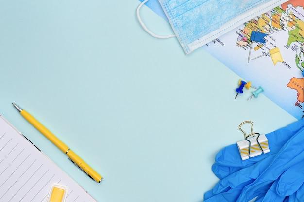 Planificación de viajes después del fin del concepto de cuarentena. cuaderno, artículos estacionarios, mapa, máscara médica y guantes sobre fondo azul con espacio de copia. planificación de viajes