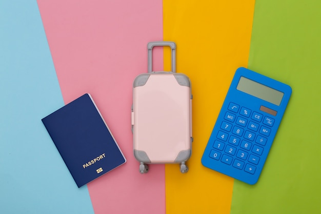 Planificación de viajes. mini equipaje de viaje de juguete, pasaporte y calculadora.