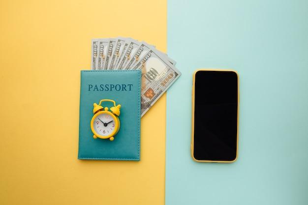 Planificación de viajes con teléfono inteligente, reloj despertador y pasaporte con dinero en superficie amarilla azul