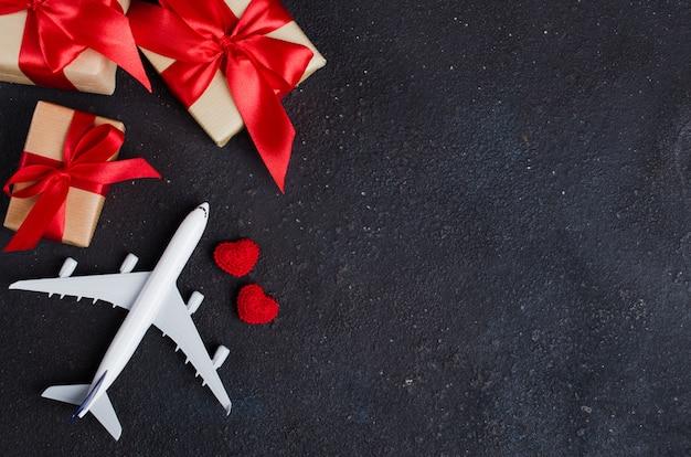 Planificación de viajes de vacaciones. concepto de viaje. modelo de avión, cajas de regalo y corazones rojos sobre fondo oscuro.