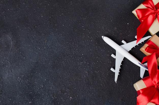 Planificación de viajes de vacaciones. concepto de viaje de regalo. modelo de avión, cajas de regalo y corazones rojos sobre fondo oscuro.