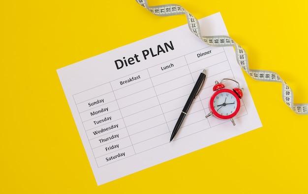 Planificador de dieta, cinta métrica, bolígrafo y alarma vista superior. es hora de comenzar un concepto de dieta