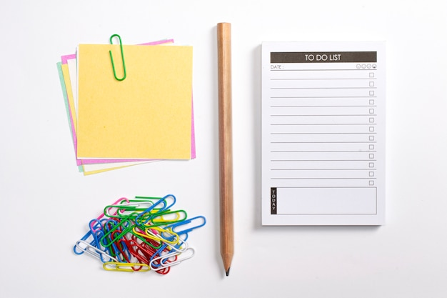 Planificador de lista en blanco para hacer con lista de verificación, lápiz de madera, clips de papel coloridos y papeles de nota aislados sobre fondo blanco.