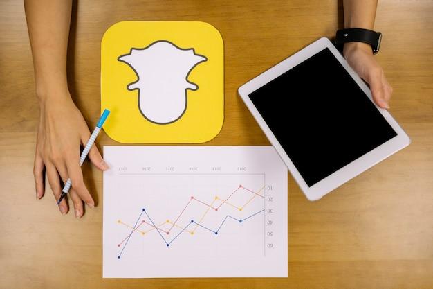 Planificador de medios sociales analizar el gráfico de snapchat con tableta digital