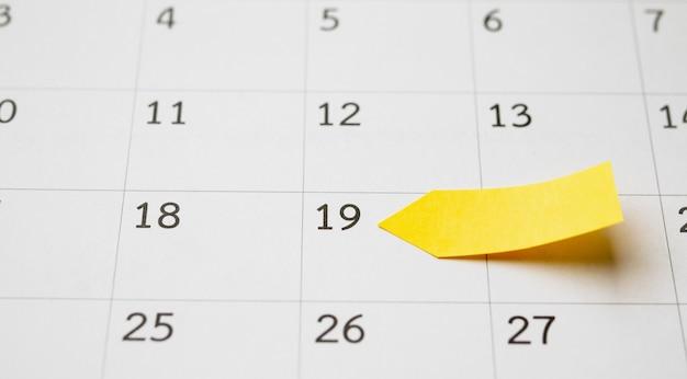 Planificador de papel adhesivo adhesivo adhesivo amarillo en blanco con espacio en la pared de la página del calendario para el concepto de reunión de cita de planificación empresarial