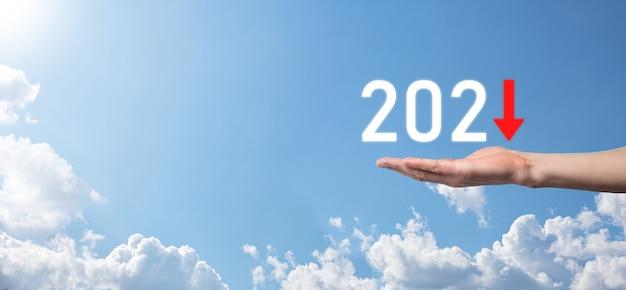 Planifique el crecimiento negativo del negocio en el concepto del año 2021. el plan de empresario y el aumento de los indicadores negativos en su negocio, disminuyen los conceptos de negocio. asimiento de la mano sobre fondo de cielo.