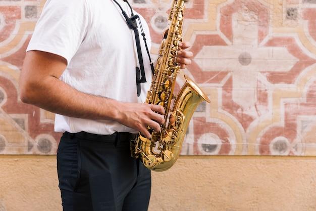 Plano americano de hombre de perfil tocando el saxofón sobre fondo geométrico