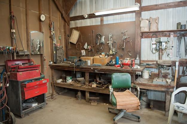 Plano amplio del banco de trabajo de un antiguo granero con diferentes tipos de herramientas