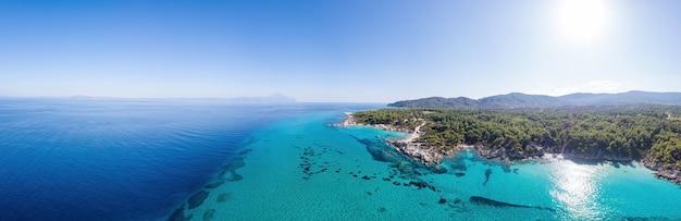 Plano amplio de la costa del mar egeo con agua azul transparente, vegetación alrededor, vista desde el drone pamorama, grecia