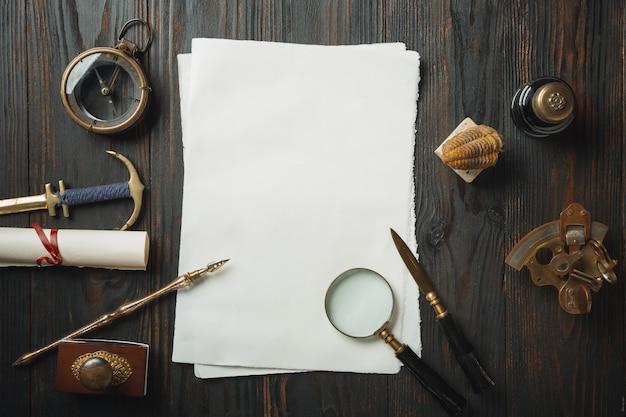 Plano antiguo sentar con letras accesorios de escritura sobre mesa de madera oscura. hojas blancas, bolígrafo, sello, paquete, tinta. estilo vintage, steampunk, concepto de luz de gas. lupa y brújula.