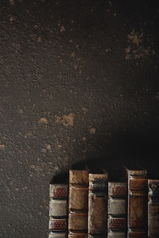 Plano antiguo sentar con pila de libros encuadernados en cuero antiguo contra una pared oscura. literatura, lectura, concepto de educación. estilo retro, vintage. copyspace para su anuncio. archivo antiguo.