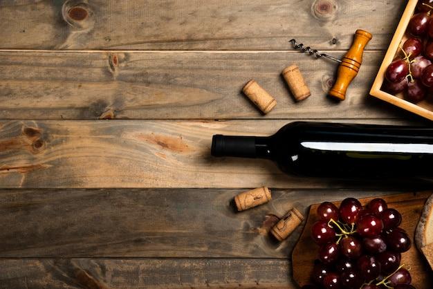 Plano de una botella de vino rodeada de corchos y uvas rojas.
