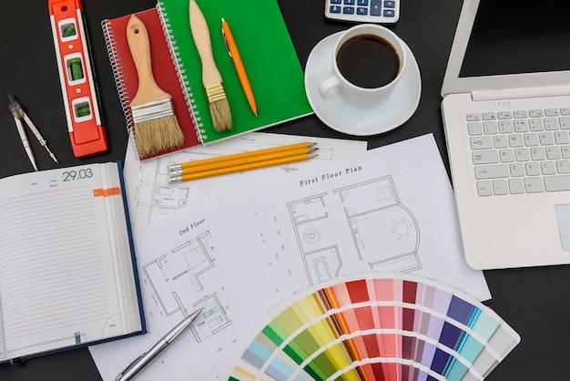 Plano de la casa, herramientas, paleta de colores y café.