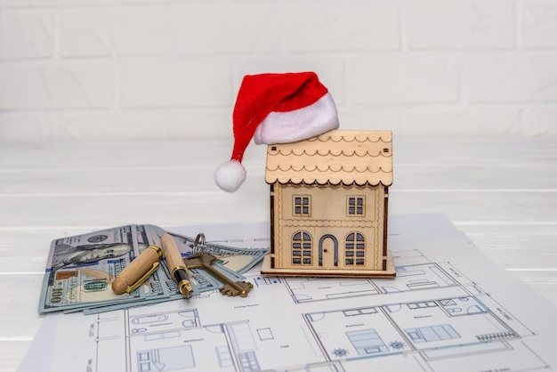 Plano de la casa con modelo de casa, dólares y llave.