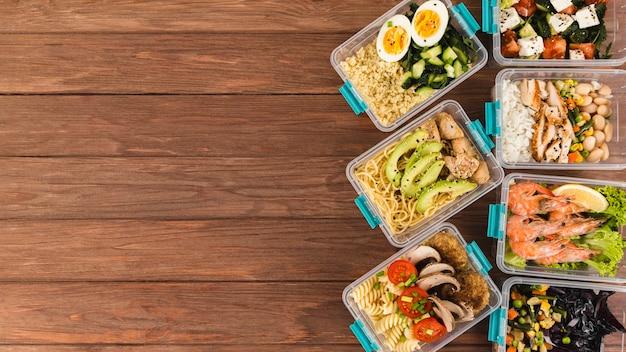 Plano de cazuelas de plástico con comidas y espacio de copia