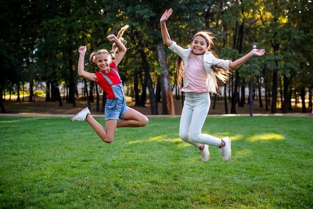 Plano completo de chicas saltando al aire libre