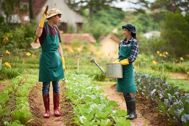Plano completo de dos granjeros conversando en medio del jardín