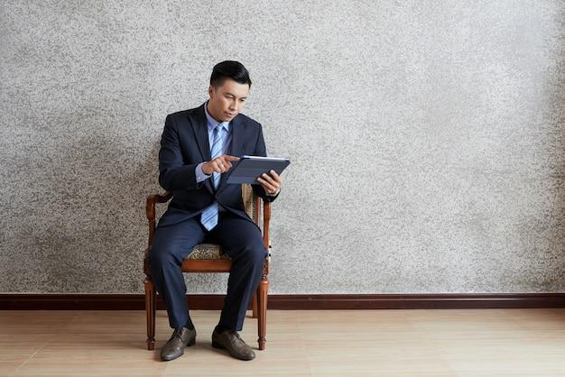 Plano completo del empresario asiático con tablet pc sentado en el sillón en una habitación vacía