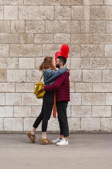 Plano completo de la feliz pareja abrazándose