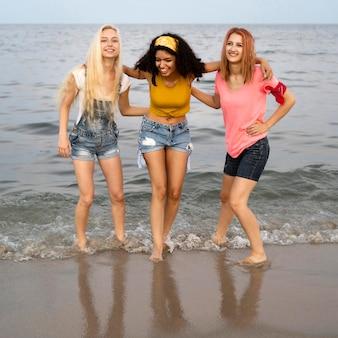 Plano completo de hermosos amigos en la playa