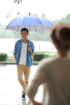 Plano completo del hombre de pie con paraguas bajo la lluvia esperando su cita