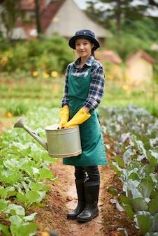 Plano completo de una joven jardinera de pie entre las camas de plantas con un embudo
