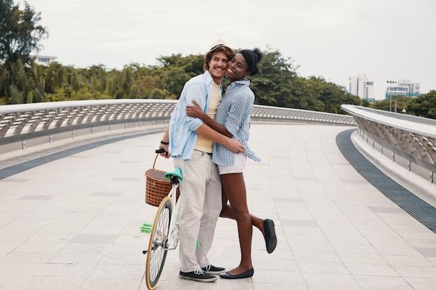 Plano completo de la joven pareja étnica abrazando a la bicicleta en el puente